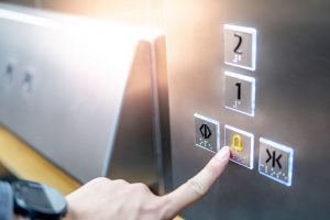 Male hand pressing on emergency button in elevator